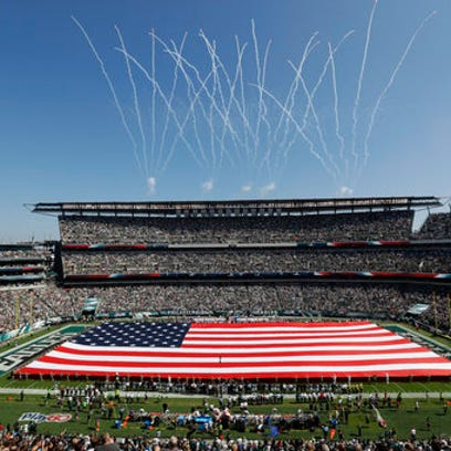 An American flag covers the field before an NFL football