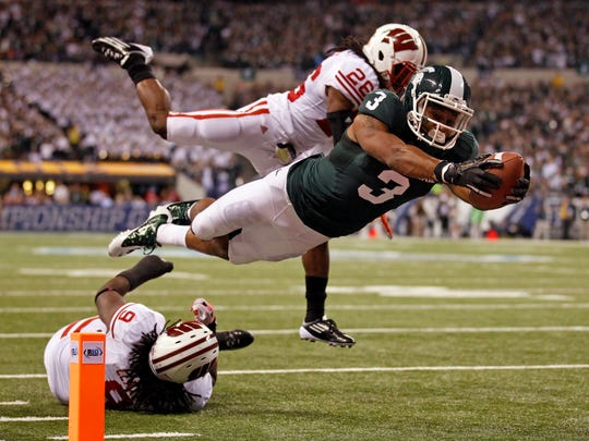 This Dec. 3, 2011, file photo shows Michigan State's B.J. Cunningham (3) diving into the end zone for a touchdown in front of Wisconsin's Antonio Fenelus during the Big Ten conference championship NCAA college football game , in Indianapolis.  The eighth-ranked Spartans finally renew their series with 11th-ranked Wisconsin on Saturday _ their first meeting in East Lansing since that Hail Mary. Both teams already have notable wins this season, Michigan State over Notre Dame and Wisconsin over LSU.