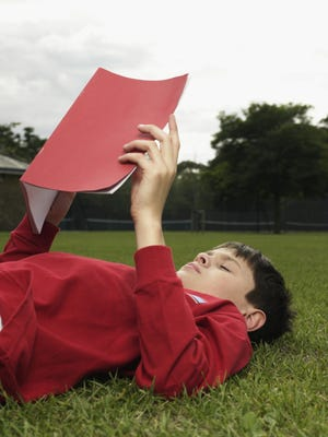 Boy with a notebook in park