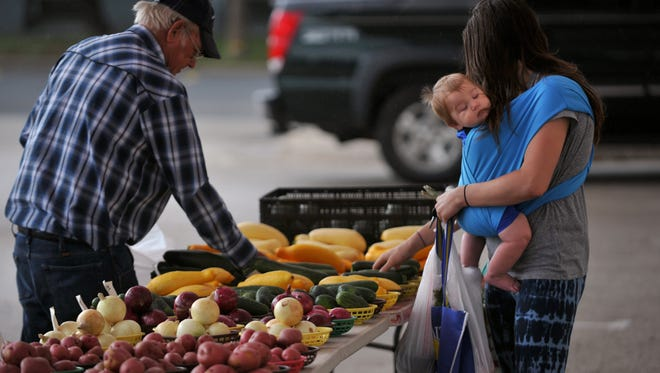 Nine-month-old Axel Halfacer rests against his mother Deserea as John Steele helps her pick out produce at the Abilene Farmers Market in June 2017.