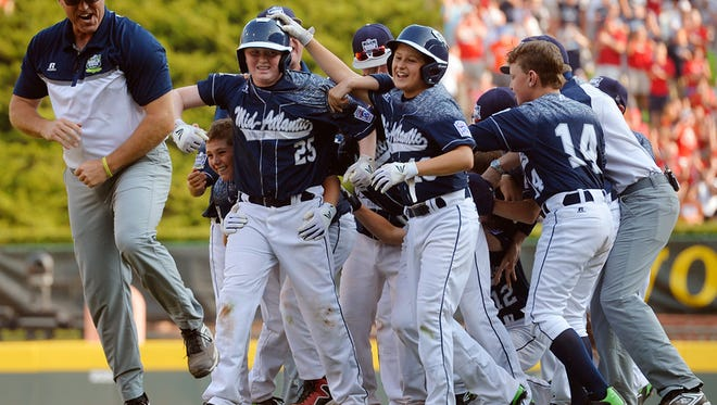 """""""Red Land's Chayton Krauss (25) is surrounded by his teammates after hitting the walk-off run Saturday, Aug. 29, 2015, after the Little League World Series U.S. championship game featuring Red Land Little League of Pennsylvania and Pearland West Little League of Texas, in South Williamsport. Red Land defeated Pearland 3-2 in a walk-off victory to move on to the world championship game against Tokyo Kitasuna of Japan."""