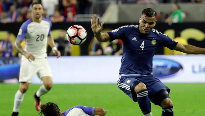 Argentina defender Gabriel Mercado, right, gets around a tackle by United States midfielder Graham Zusi during a Copa America Centenario semifinal soccer match Tuesday in Houston.