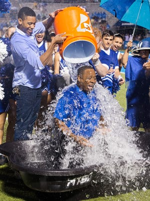 MTSU President Sidney A. McPhee is doused with a cooler of ice water for his ALS Ice Bucket Challenge by MTSU Student Body President Andrew George, left, during the home football opener against Savannah State.