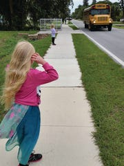Children wait safely after  sidewalks were put in at the Villas.