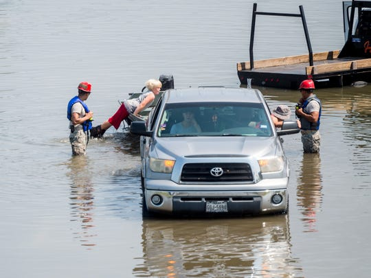 A family is rescued from their car Friday in Port Arthur, Texas. on Sept. 1.   Houston was limping back to life on Friday one week after Hurricane Harvey slammed into America's fourth-largest city and left a trail of devastation across other parts of southeast Texas. As flood waters receded in Houston and residents began slowly returning home other nearby towns such as Rockport, Beaumont and Port Arthur were struggling to get back on their feet. / AFP PHOTO / Emily KaskEMILY KASK/AFP/Getty Images ORIG FILE ID: AFP_S15TT