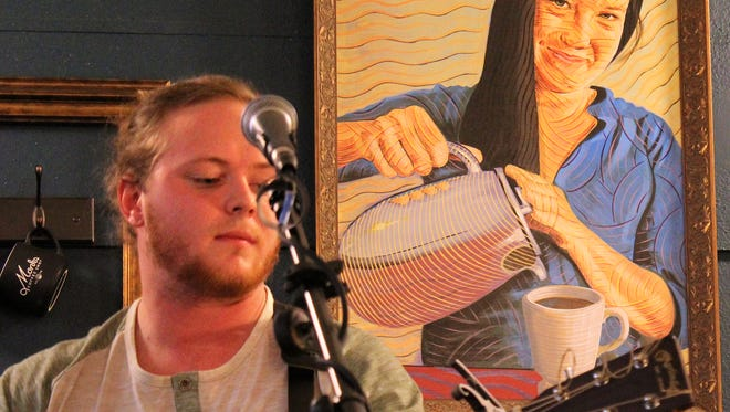 Andrew Holmes performs under the watchful eye of Monks owner Allison Carroll during his album release event Nov. 18 at the downtown Abilene coffee shop.