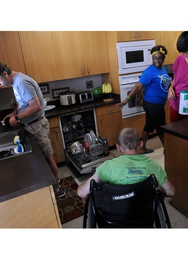 House manager Tanya Whitaker (in blue) gestures to the dishwasher as Jay Blay rinses the dinner dishes in the sink, Patrick Ludwig (center) listens and Lori Hester prepares to wipe the counters July 18, 2017. The home is on the Disability Resources, Inc. campus,  resident assist in keeping the home clean.