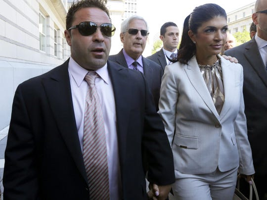 """The Real Housewives of New Jersey"" stars Giuseppe ""Joe"" Giudice (left) and his wife, Teresa Giudice, of Montville walk out of Newark court after an appearance. (AP Photo/Julio Cortez, File)"