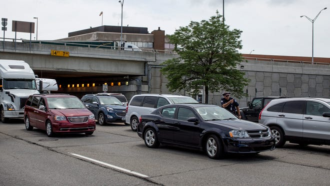 A Customs and Border Protection officer instructs drivers to move as they block northbound lanes on Pine Grove Avenue attempting to cut into the left-turn for the ramp to the Blue Water Bridge in Port Huron. Customs is advising travelers to be aware of increased traffic during the Labor Day weekend.