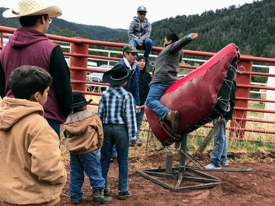 A youngster tries out riding a mechanical bull at the