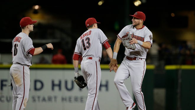 Arizona Diamondbacks' David Peralta, right, celebrates with Nick Ahmed (13) and Chris Owings after the team beat the Seattle Mariners in a baseball game Tuesday, July 28, 2015, in Seattle. The Diamondbacks won 8-4.