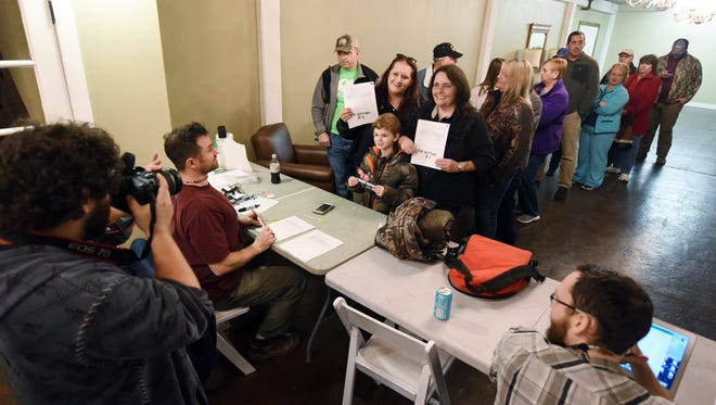"""Paula Westbrook, of Picayune, center left, friend Cheryl Mitchell, of Magee, and Mitchell's grandson, Matthew Mitchell, 7, have their photograph taken as they check in for the filming of a town hall meeting at the Ice House in Jackson on Tuesday for an upcoming episode of the Animal Planet reality TV series, """"Finding Bigfoot."""""""