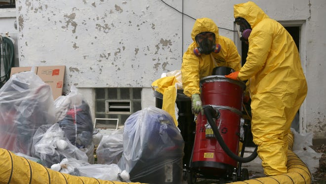 Environmental cleanup crews work in a house on the corner of West Sixth Street and Rowland Avenue where a mercury spill occurred.