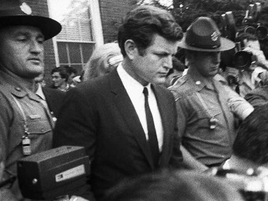In a July 25, 1969, photo, Sen. Edward Kennedy is escorted by troopers as he leaves court in Edgartown, Massachusetts, after pleading guilty to a charge of leaving the scene of the accident which killed aide Mary Jo Kopechne.