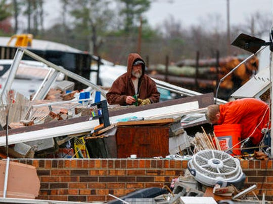 In this Nov. 30, 2016, photo, Gregg Jefferey, left, and his son Tyler help a family friend clean up their business at Rosalie Plaza after a possible tornado ripped through the town in Rosalie, Ala. The most extreme tornado outbreaks, like the deadly one Tuesday in the Southeast, are mysteriously spawning many more twisters than they did decades ago, a new study claimed. The same type of once-every-five-years-or-so outbreak that 50 years ago had about 12 tornadoes, now has on average about 20, said Columbia University applied physics professor Michael Tippett, lead author of the study in Thursday's journal Science.