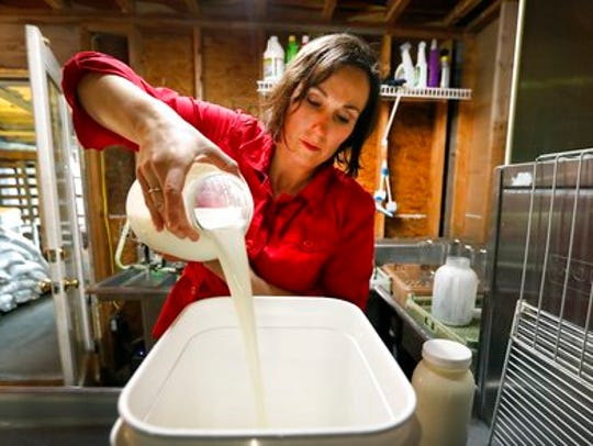 In this March 24, 2017 photo, Rachel Moser pours raw milk into a container on her Be Whole Again Farm in Excelsior Springs, Mo.