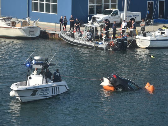 Airbags inflate under water enabling the submerged Buick Lucerne to rise to the surface and towed by boat to Sawyer Park boat landing in Sturgeon Bay on Thursday. The car rolled into the water at CenterPointe Yacht Services. A passenger managed to escape, but the driver died.