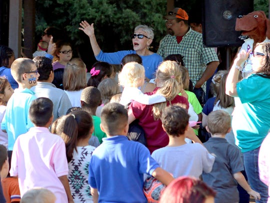In this file photo, Bettye Ricks (center) leads a group of children in Camp Fire songs for their parents during the organization's annual Fall Family Fun Night at Harrell Park.