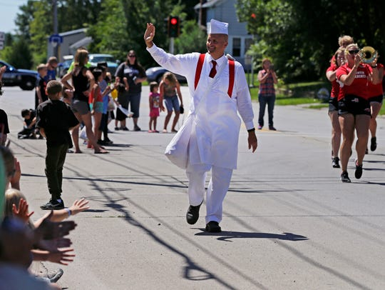 "John Steltz as ""Hamburger Charlie"" waves to the crowd"