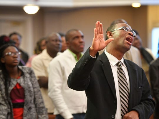 Pastor Maromy Samuel worships during his Haitian congregation's