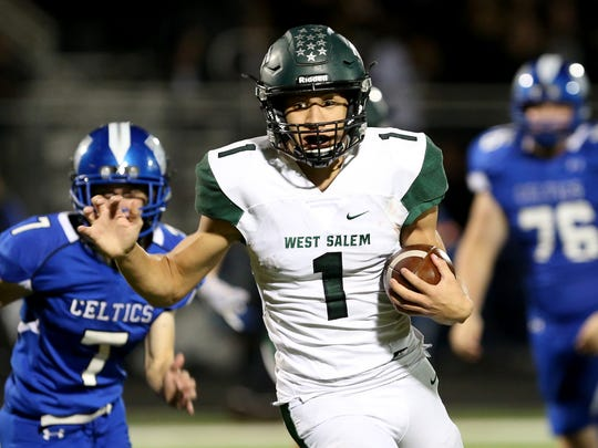 West Salem's Simon Thompson (1) rushes past McNary's Robert Benson (7) and Devin Meyer (76) in the West Salem vs. McNary football game at McNary High School in Keizer on Friday, Oct. 27, 2017. West Salem won the game 57-6.