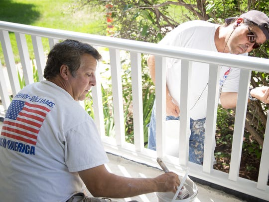 Carlos Fernandez, left, and Joe Fernandez paint the front porch of C.M. Russell's original residence Monday. Restorations to the house are taking place this summer and include re-shingling the roof and improving the historical accuracy of the interior.