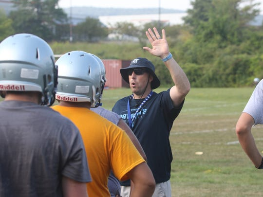 John Jay High School football coach Tom O'Hare gives instructions to players during practice on Wednesday.