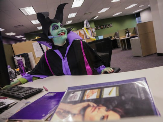 TNG Worldwide sales member Samantha Perreault takes a call while dressed as Disney character Maleficent while taking part in office Halloween festivities at TNG Worldwide headquarters in New Hudson on Oct. 31, 2013.