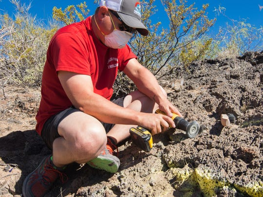 Friends of Organ Mountains-Desert Peaks executive director, Benjamin Gabriel uses a wire brush to clean up grafitti on the rock face of Kilbourne Hole.