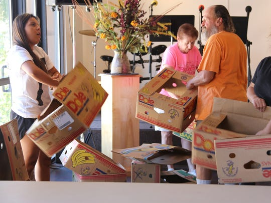 Volunteers unload food to give to local families during