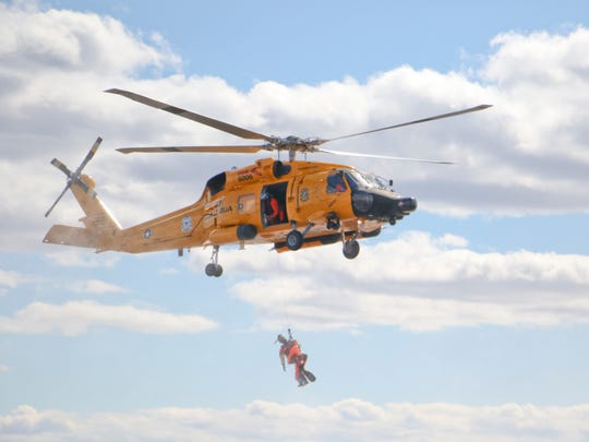 A rescue swimmer hangs below an MH-60 Medium Range Recovery Helicopter Friday, Feb. 26, 2016, during a search and rescue demonstration near Elizabeth City, N.C. U.S. Coast Guard helicopters were painted the retro color scheme to celebrate the Coast Guard's aviation centennial birthday.