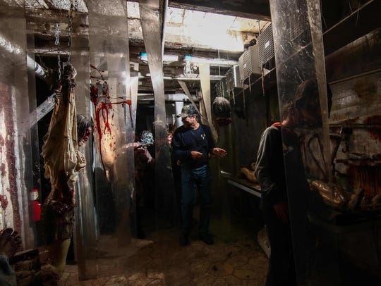 Guests move through a haunted house attraction at Frightland