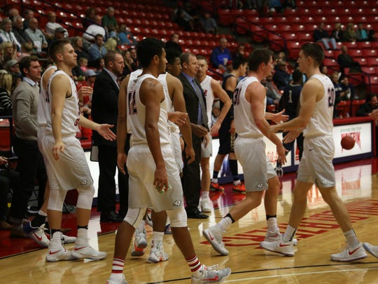 Dixie State players congratulate each other after beating NDNU 77-69 Saturday night inside the Burns Arena.