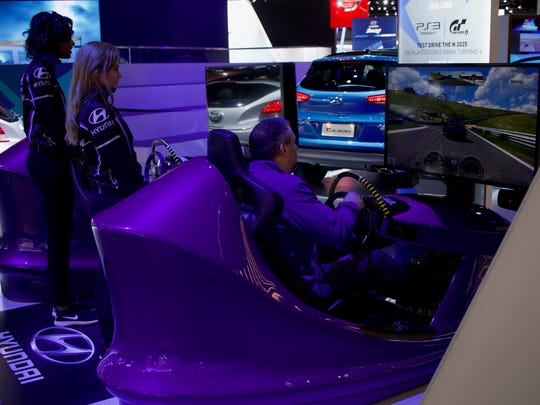 "A member of the press tries out the Hyundai racing challenge, playing a game of ""Gran Turismo 6"" on PlayStation 4, inside the North American International Auto Show showroom on Jan. 10, 2016 at Cobo Center in Detroit."