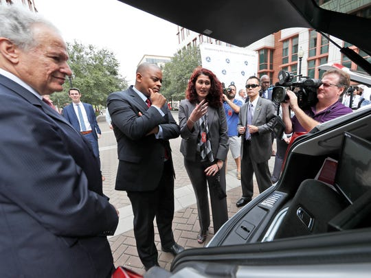 NHTSA Administrator Mark Rosekind, left, and Transportation Secretary Anthony Foxx, listen to Myra Blanco, with Virginia Tech's transportation Institute, talk about their car after a news conference about self-driving cars, Tuesday, Sept. 20, 2016, in Washington.