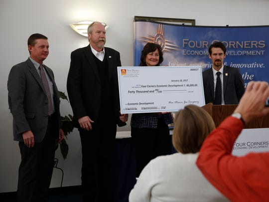 Randy Fitzpatrick, left, area manager for the New Mexico Gas Co.; Clifton Horace, chairman of the Four Corners Economic Development board; Mary Homan, economic development and community affairs manager for New Mexico Gas Co.; and Warren Unsicker, the new CEO of 4CED, pose with a $40,000 check on Wednesday at the Quality Center for Business at San Juan College in Farmington.