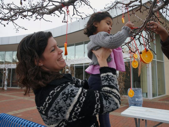 Cynthia Rapp Sandhu helps her daughter Zaira Sandhu make a wish on a tree during a Chinese New Year celebration Saturday at the Farmington Museum at Gateway Park.