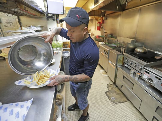 Cook Oscar Gonzalez puts together a food order in the kitchen at The Bar on Lime Kiln Road. The location will go through more than a ton of its signature chicken wings each week during March Madness.