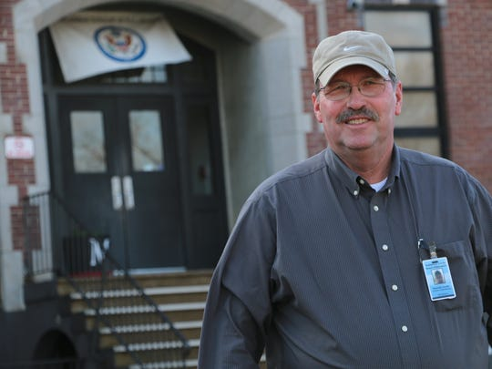 Maintenance Director Kenneth Curlee stands in front of McFadden School, where he and his granddaughters attended.
