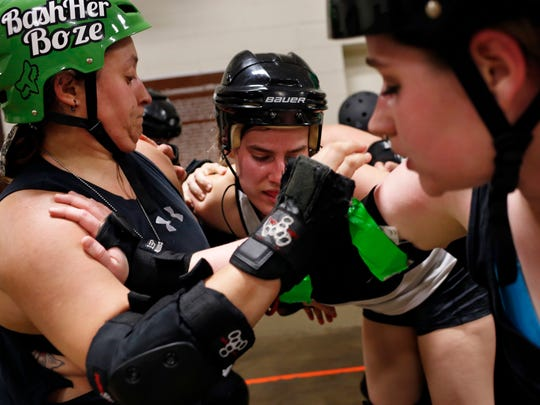 """Capital City Roller Girls' Ashley Bleicher, akaTrack Queen, center, attempts to break through the group during practice. Players are just as tough during practice as they are during games. """"I'd be more upset if you had taken it easy on me,"""" player Trisha Morace once said to a teammate who'd sent her flying into a stack of chairs."""