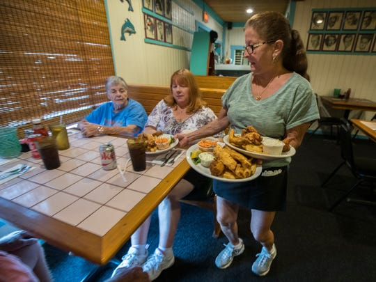 Tina Saunders tends to her lunch customers Friday, July 21 at Thirsty's in Cape Coral. Saunders has been a server at the 35-year-old restaurant  for 14 years.