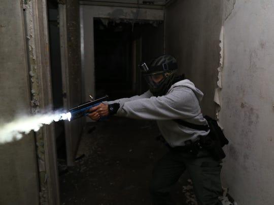 A police cadet fires a patrol gun with simunition,
