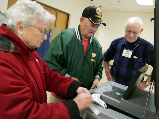 Anne and Tom Jansen cast their ballots Tuesday with help from poll worker Bob Smith, right, in Kaukauna.