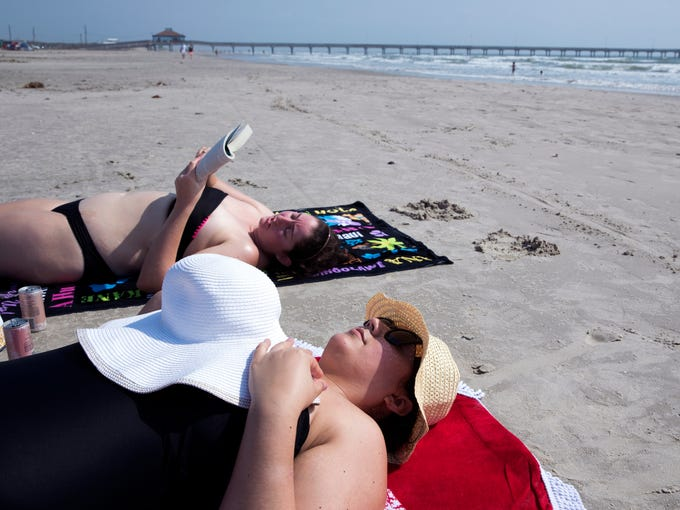 Haley Turpin (left) reads to Krystal Duran on the beach