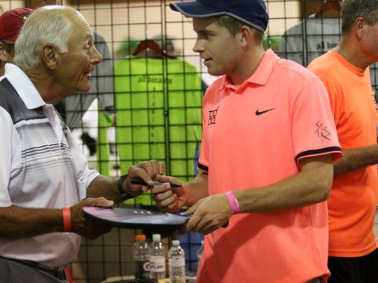 Kyle Yates, right, signs a fan's pickleball paddle during the Pickleball Global Challenge Cup at Tennis US on Saturday, March 31, 2018.
