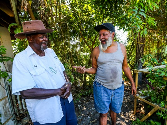 Jay Parson, left, talks collard greens and composting with Patrick Caldwell of Lazy Man's Garden at Parson's home in Fort Myers. Parson, who was raised on a farm in the Carolinas, turned his yard into one big container farm that Caldwell inspired his urban farming ideas.