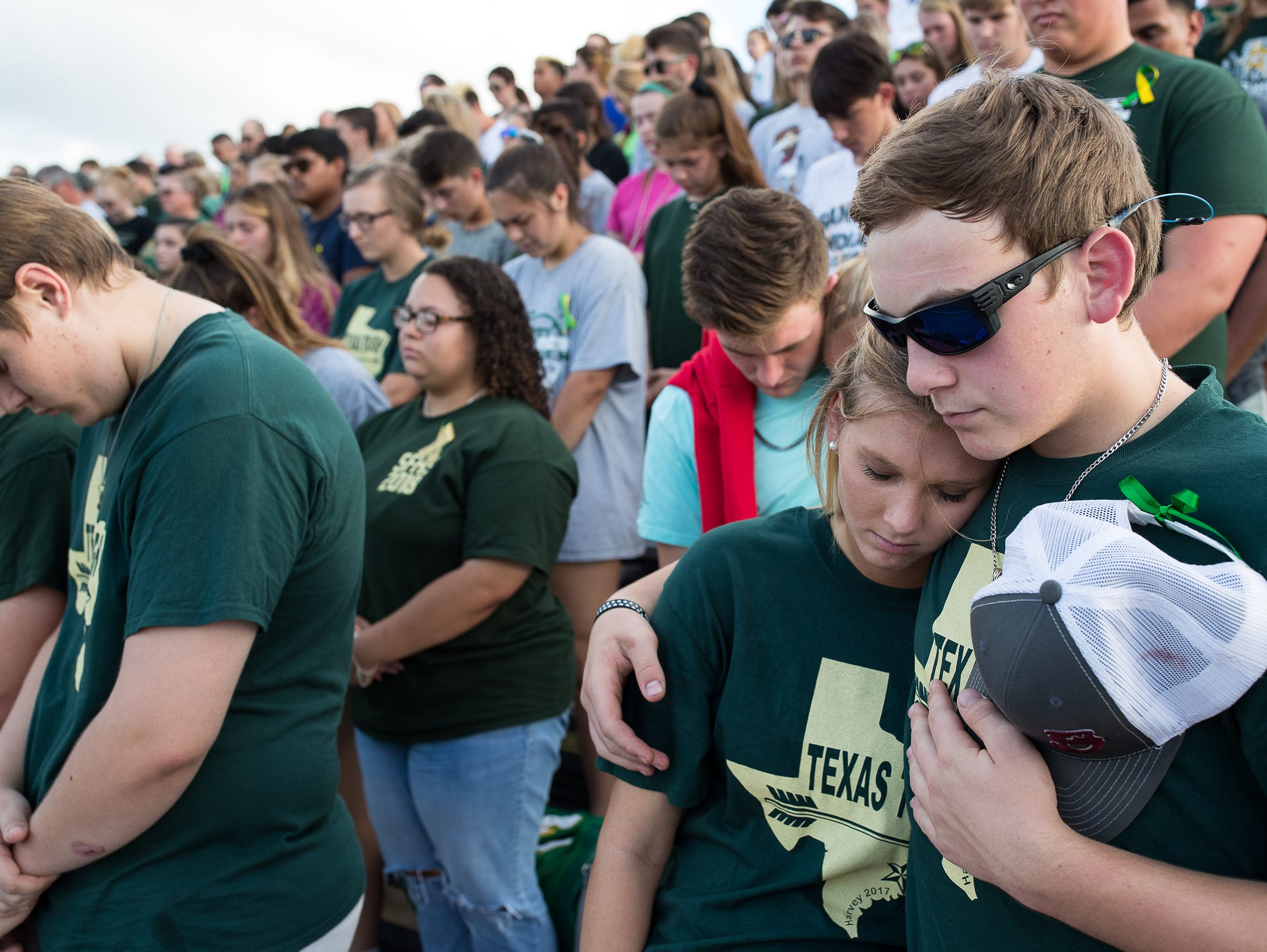 Santa Fe students bow their heads during a moment of silence before a baseball playoff game against Kingwood Park to honor the 10 who died in Friday's shooting at Santa Fe High School.