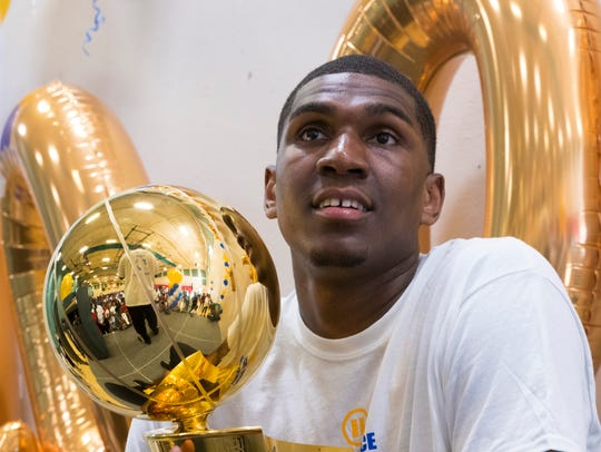 Kevon Looney holds this year's NBA Championship trophy
