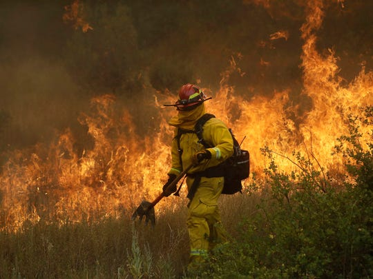 A firefighter with Cal Fire Mendocino Unit walks along a containment line as a wildfire advances on July 30 in Lakeport.