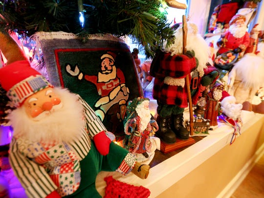 A Santa Claus collection including a rug Tom Anderson and Tass Morrison bought on their trip to China fill a window bench in their dining room.